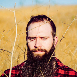 Image of a the author as a bearded hipster in tall grass.